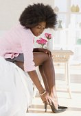 Woman with afro putting on her heels