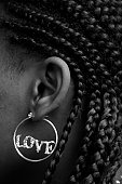 Woman With Cornrows Wearing Earring That Spells Love