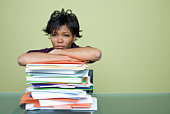 Overworked woman with stack of files