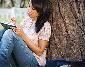 Woman sitting against tree writing in notebook